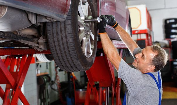 Elderly man mechanic engaged in replacement of car wheel in auto workshop