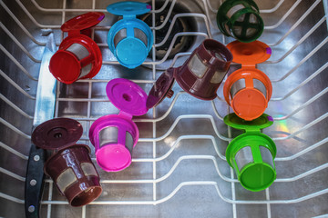 Stainless steel sink with dish drainer drying brightly colored refillable coffee pods