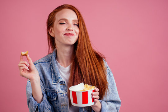 cute red long foxy haired ginger woman holding packaging cardboard box bucket with french fries and eating chicken crunchy nuggets in pink studio