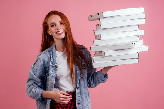 pretty long ginger red-haired woman holding a lot of boxes with fast food snack isolated pink background studio shot. delivery for home party concept
