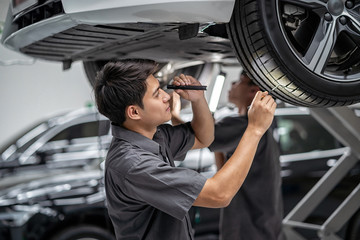 Asian mechanic Checking and torch tire in maintainance service center which is a part of showroom, technician or engineer professional work for customer, car repair concept
