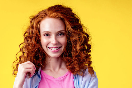 curly redhaired ginger woman with snow white smile brackets on teeth touching a new hairstyle in studio yellow background