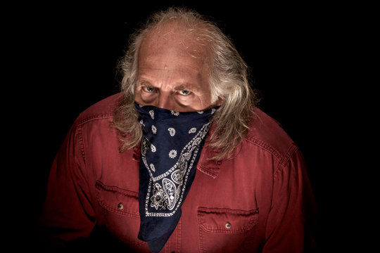 A long haired masked man wearing a blue bandana to cover the face and a red shirt , hunched over and looking intently at viewer with dark background