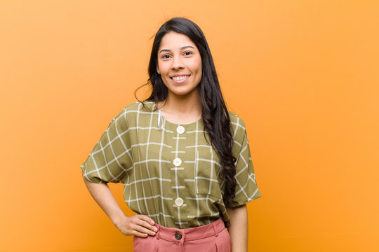 young pretty hispanic woman smiling happily with a hand on hip and confident, positive, proud and friendly attitude against brown wall