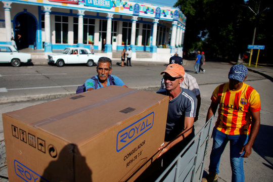 Taxi driver Orlando Cervantes loads his trailer car with a freezer bought from a shop selling products for dollars in Havana