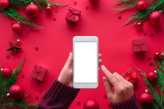 Female hand hold phone on merry christmas red background, girl customer shopper using online mobile shopping app choosing holiday gifts with mobile payments on mock up white screen, close up top view