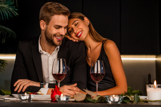 Excited loving couple celebrating special event with wine and candles , having dinner together