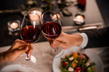 Printed kitchen splashbacks Restaurant Close up of young couple toasting with glasses of red wine at restaurant