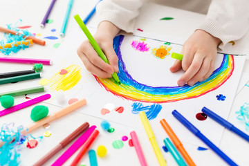 Child draws a rainbow with markers. Creative activities in kindergarten.