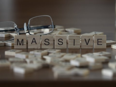 The concept of Massive represented by wooden letter tiles