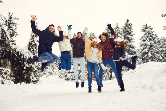Friends jumping in the snow in the park in winter