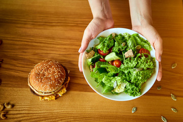 Woman decides eating hamburger or fresh salad in kitchen. Cheap junk food vs healthy diet