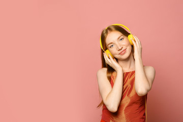 Portrait of beautiful young woman with headphones on pink background, space for text Wall mural