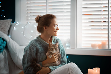 Young woman with cute cat at home. Cozy winter