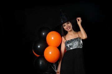 Beautiful woman wearing witch costume with balloons for Halloween party on black background, space for text Wall mural