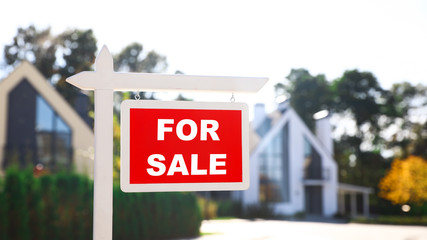 Red real estate sign near house outdoors on sunny day