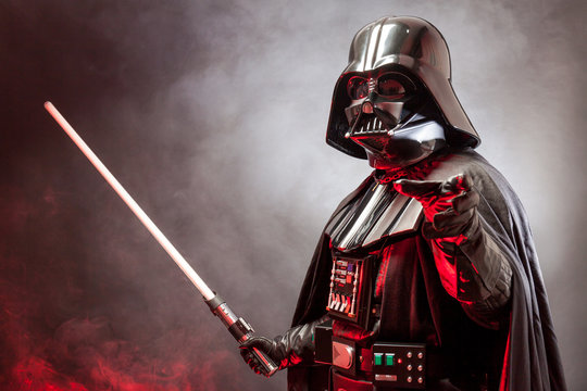 SAN BENEDETTO DEL TRONTO, ITALY. MAY 16, 2015.  Half-lenght portrait of Darth Vader with his sword and grab hand . Darth Vader is a fictional character of Star Wars saga. Black background.