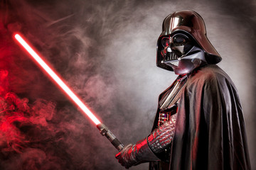 SAN BENEDETTO DEL TRONTO, ITALY. MAY 16, 2015. Portrait of Darth Vader costume replica with his sword . Lord Fener is a fictional character of Star Wars saga. Red grazing light and smoke
