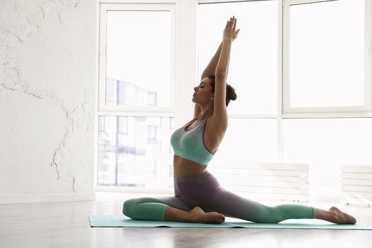 Young woman practicing half pigeon asana in yoga studio. Ardha Kapotasana pose
