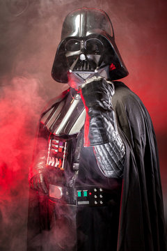 SAN BENEDETTO DEL TRONTO, ITALY. MAY 16, 2015. Close up of  helmet of Darth Vader costume replica with fist punch . Darth Vader is a fictional character of Star Wars saga.  Red grazing light and smoke