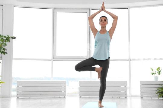 Young woman practicing tree asana in yoga studio. Vrksasana pose