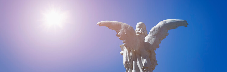 Fototapete - Rear view of antique statue angel in sunlight as a symbol of strength, truth and faith.