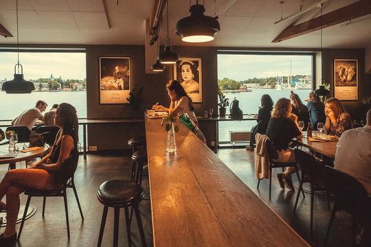 STOCKHOLM, SWEDEN - JUN 16, 2018: People drinking inside restaurant of the cultural center Fotografiska on June 16, 2018. Sweden with 10,5 million people ranks high in life expectancy