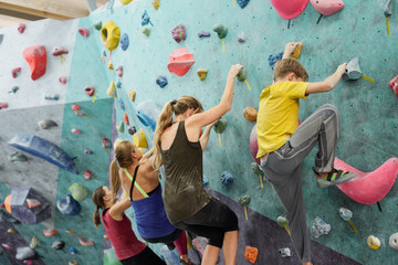Young sportswomen and schoolboy in activewear creeping upon climbing wall