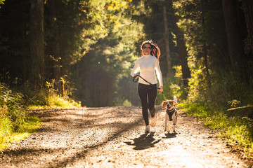 Keuken foto achterwand Jogging Girl is running with a dog (Beagle) on a leash in the autumn time, sunny day in forest. Copy space in nature