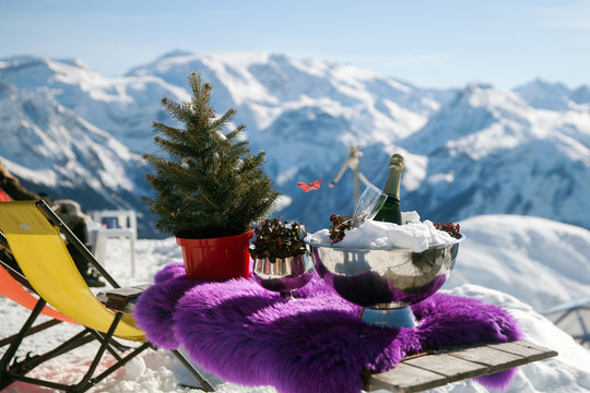 A bottle of champagne and a glass in ice on table in mountains, France