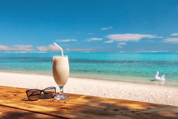 Coconut shake pina colada drink cocktail milkshake at beach bar in Bora Bora island, Tahiti, French Polynesia. Ocean view with tall milk drinking glass on table.