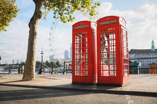 Two London Telephone Boxes on an Empty Street by the River Thames