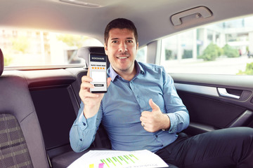 Mature businessman sitting on backseat of car rating taxi services on app while commuting to work – business on the go