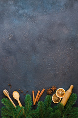 Christmas culinary background for menu or recipe. Spices for baking and fir branches on concrete.