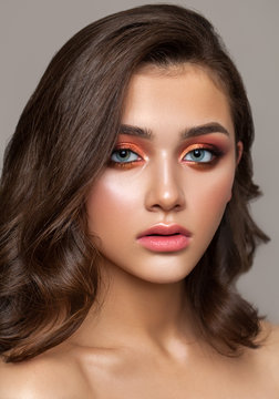 A very beautiful young girl with colorful trendy smoky eyes, bright blue eyes and natural wavy hairdo.