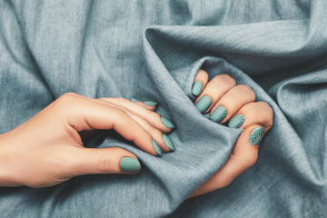 Wall Mural - Close up view of woman hands with trendy manicure on jeans cloth background.