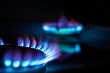a hundred dollar bill on a gas burner with a burning fire on a black background, the front and back background is blurred with a bokeh effect