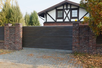brown wooden gate and brick fence in the autumn street