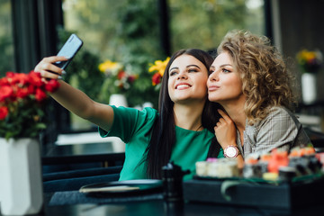 Pretty girls, partners taking a picture by the cell phone with sushi plate on table. Selfie time.