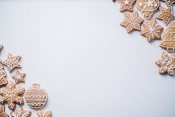 Christmas background with homemade gingerbread cookies on white table, copy space. Festive food,...