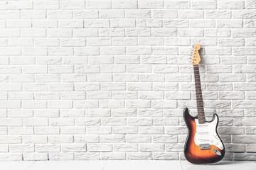 Modern bass guitar near white brick wall