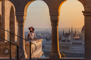 A happy young woman enjoying her trip to the Castle of Budapest in Hungary on the view point from Fisherman Bastion on sunrise.