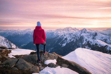 Foto auf Leinwand Rosa hell Young woman in snowy mountains at sunset in winter. Beautiful slim girl on the mountain peak against snow covered rocks and colorful red sky with clouds in the evening. Travel in Dolomites. Tourism