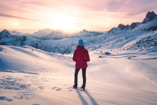 Young woman in snowy mountains at sunset in winter. Landscape with beautiful slim girl on the hill against snow covered rocks and colorful sky with clouds in the evening. Travel in Dolomites. Tourism.
