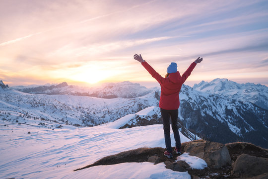 Happy young woman in snowy mountains at sunset in winter. Beautiful slim girl on the mountain peak with raised up arms, snow covered rocks and colorful sky with clouds. Travel in Dolomites. Tourism