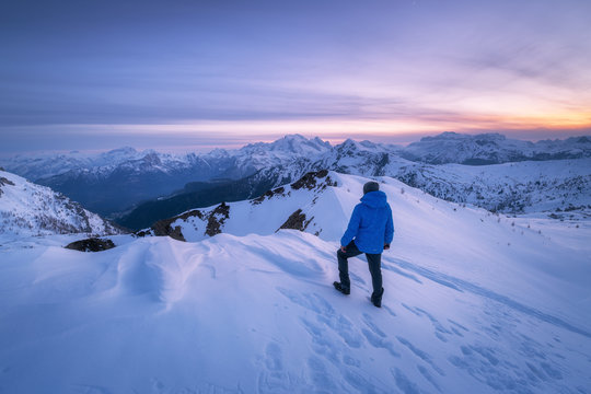 Young man in snowy mountains at sunset in winter. Sporty guy on the mountain peak, snow covered rocks and colorful blue sky with clouds at dusk. Travel in Dolomites. Wintry landscape with tourist