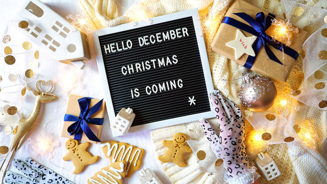On-trend stylish Christmas flat lay, cozy in bed or indoors with warm sweater, gifts and letter board spelling Hello December, Christmas is Coming.