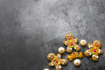 Delicious Christmas gingerbread men.Christmas baking ingredients and supplies on dark...