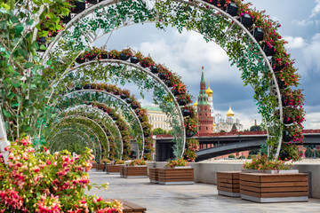 Flowers in town. Arches of flowers adorn the capital. Moscow is decorated with bouquets and flower beds. Flower design in the city. Kremlin on a background of greenery.