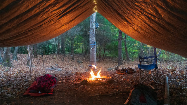 Primitive Tarp Shelter with campfire and fairy lights. Survival Bushcraft setup in the Blue Ridge Mountains near Asheville. During autumn / fall season.